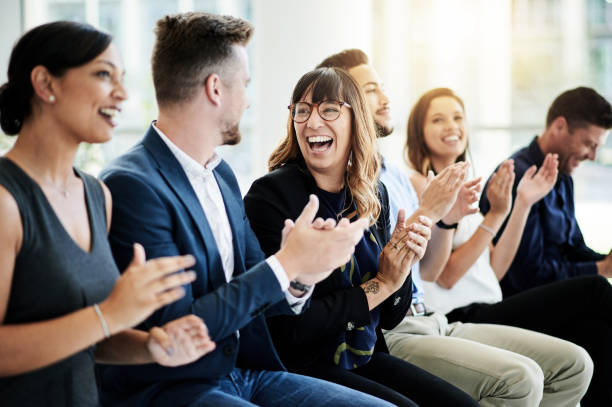 Inspire your teams to keep on achieving Shot of a group of businesspeople applauding during a seminar group corporate stock pictures, royalty-free photos & images