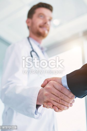 182362845 istock photo Inspired doctor shaking hands with a businessman 973701228