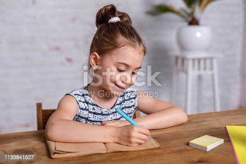 Inspired little girl at the table draw with crayons or do home work. Studying in elementary school. Home education
