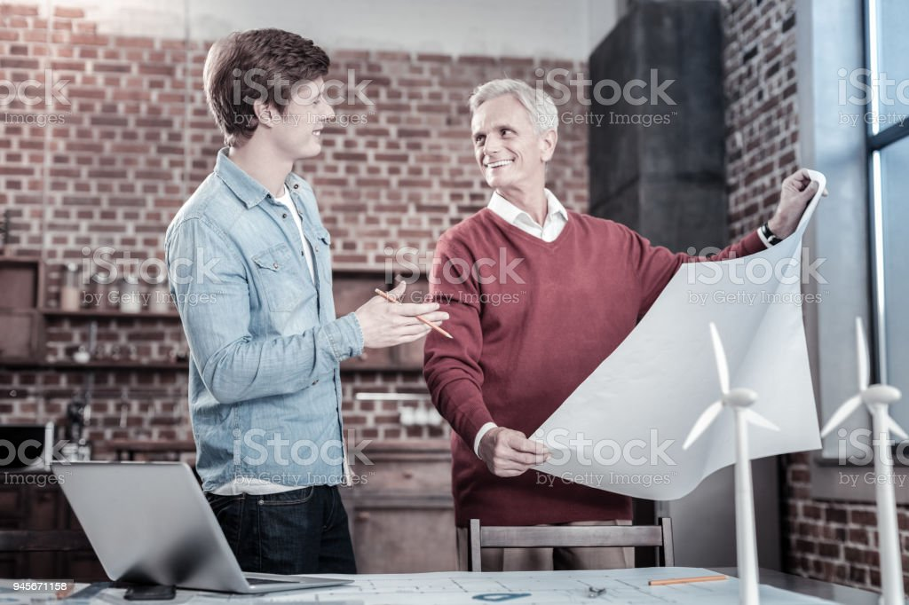 Inspired male engineers perfecting blueprint stock photo