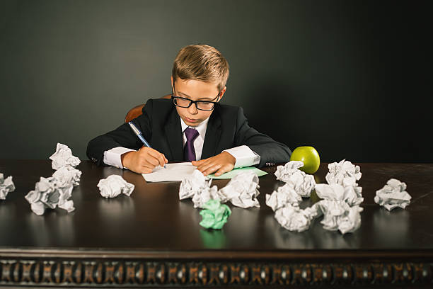 inspired school boy writing essay or exam - contributor stock pictures, royalty-free photos & images