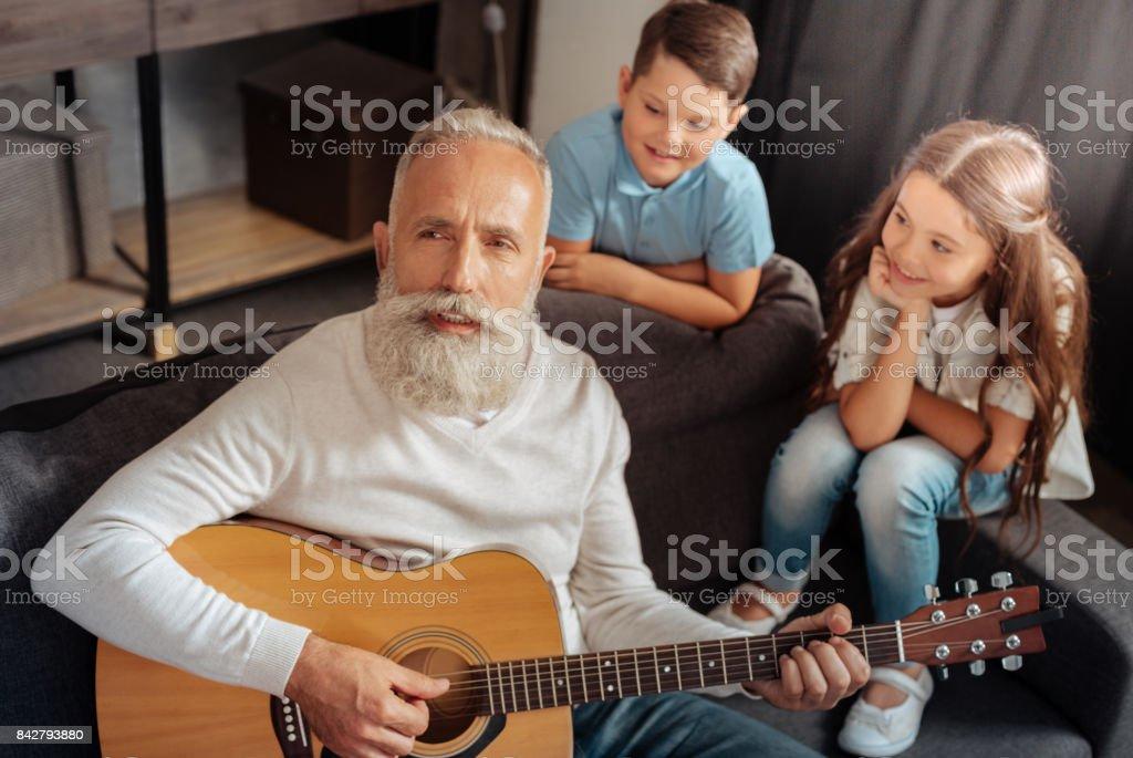 Inspired senior man playing guitar for his grandchildren stock photo
