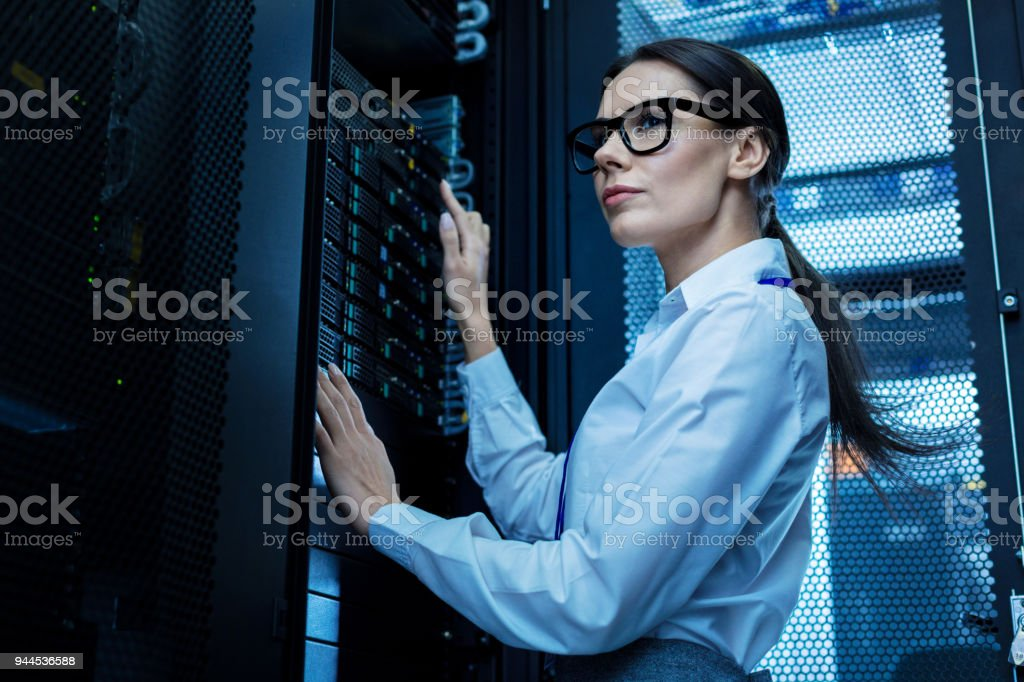 Inspired woman working in a server rack stock photo