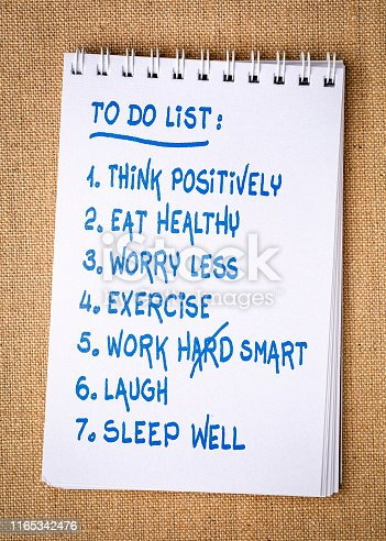 inspiring and positive to do list  - handwriting in a spiral sketchbook against burlap canvas background