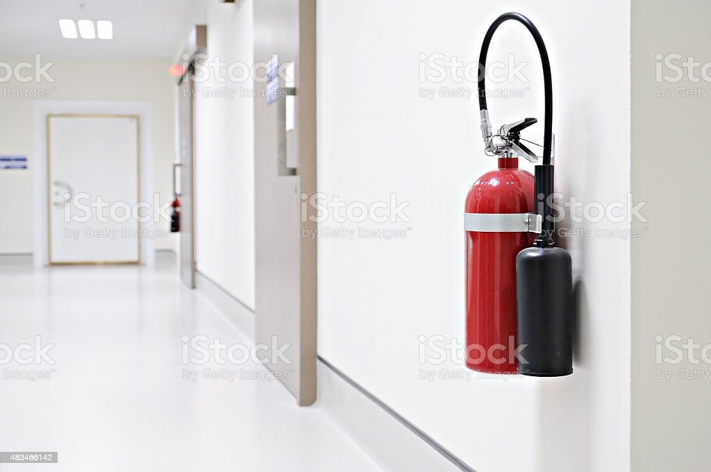 Install a fire extinguisher on the wall in buiding stock photo
