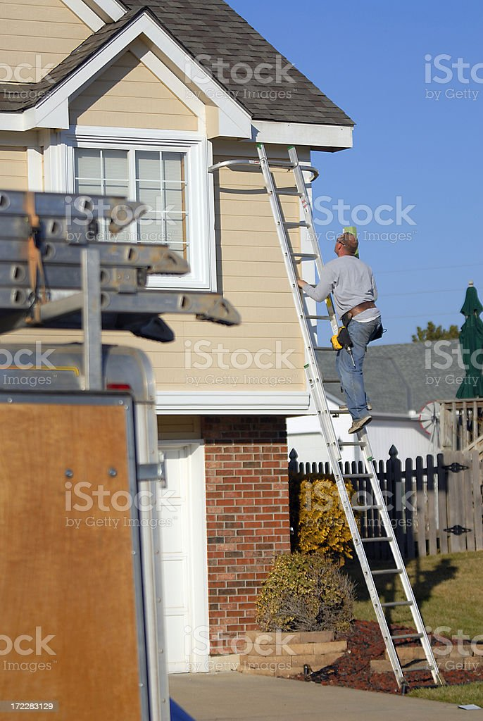 Install Home Guttering with Ladder royalty-free stock photo