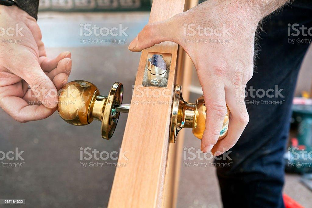 Install interior door, joiner mount knob with lock, hand close-up. stock photo