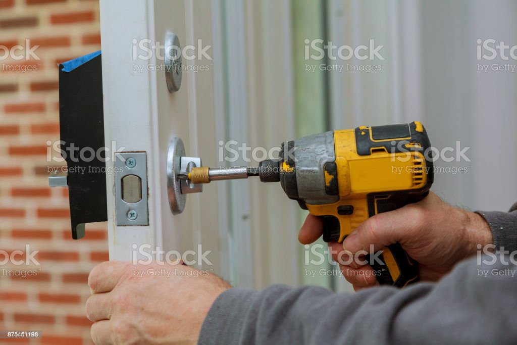 Install the door handle with a lock, Carpenter tighten the screw, using an electric drill screwdriver, stock photo
