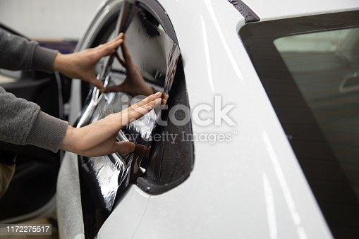 1145626150 istock photo Install windows film on the car. 1172275517