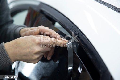1145626150 istock photo Install windows film on the car. 1172275534