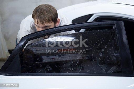 1145626150 istock photo Install windows film on the car. 1172275554