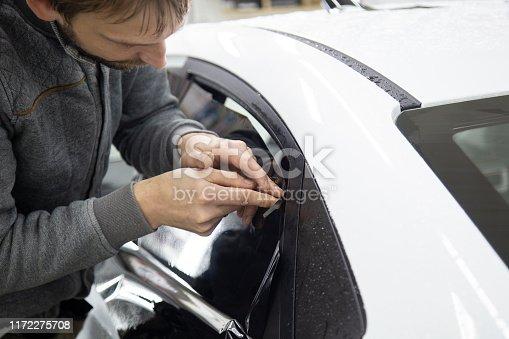 1145626150 istock photo Install windows film on the car. 1172275708