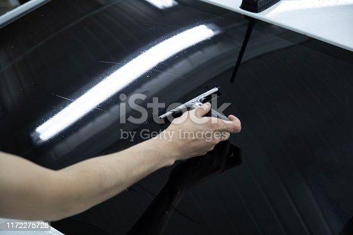 1145626150 istock photo Install windows film on the car. 1172275728