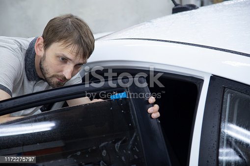 1145626150 istock photo Install windows film on the car. 1172275797