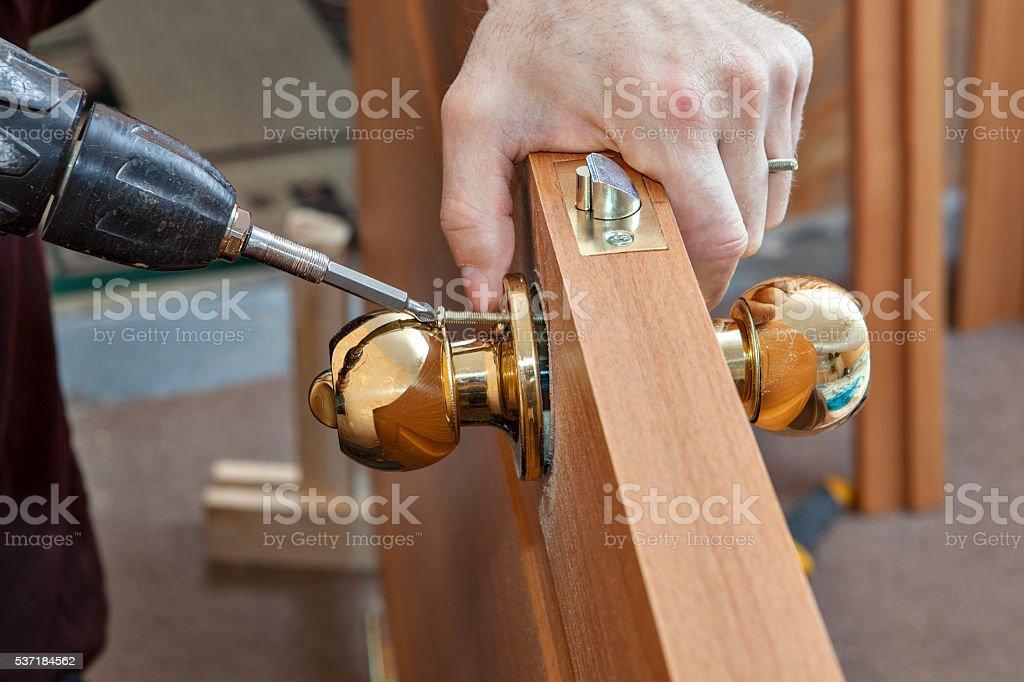 Installation door knob with lock,woodworker screwed screw, using screwdriver. stock photo