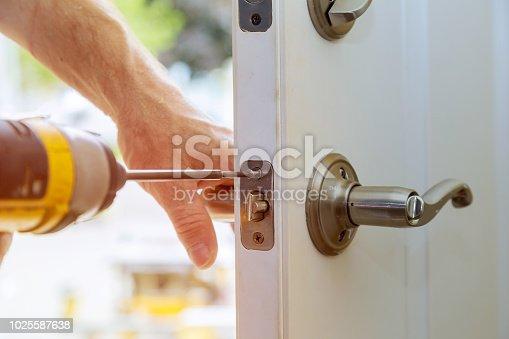 Installation locked interior door knobs, close-up wood worker hands install lock.