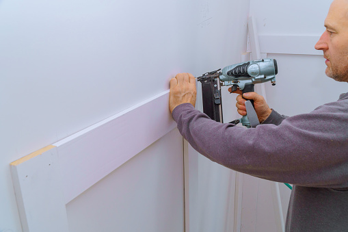 istock Installation mouldings on the wall of fragment of molding, top view of carpenter using nail gun 1089679366