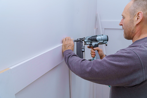 istock Installation mouldings on the wall of fragment of molding, top view of carpenter using nail gun 1217013121