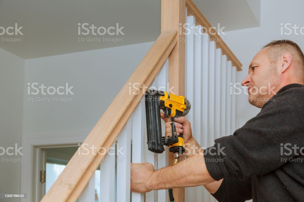 Installation nailing the railing for stairs with an air gun wooden railing stock photo