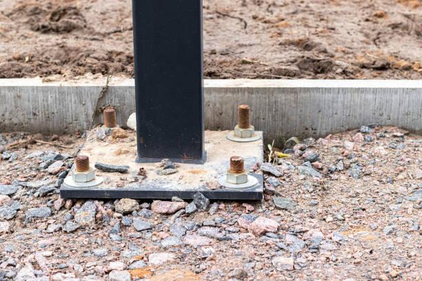 Installation d'une colonne d'éclairage ou d'un panneau d'affichage avec quatre boulons d'ancrage sur une voie d'un chantier de construction recouvert de gravier près d'un trottoir en béton - Photo