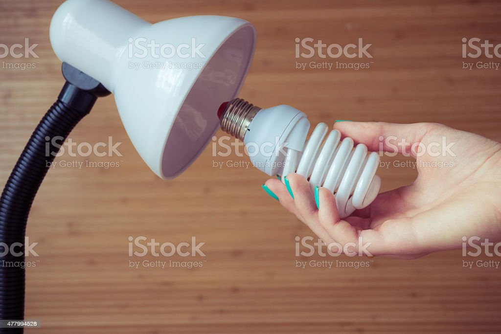 Installation of a modern economical bulb in a table lamp stock photo