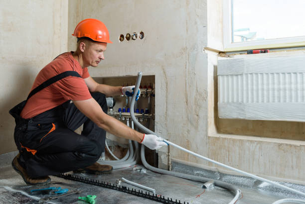 Installation of a warm floor. The worker is installing a pipe for the warm floor in the apartment. He is putting insulation on the pipe. hot spring stock pictures, royalty-free photos & images