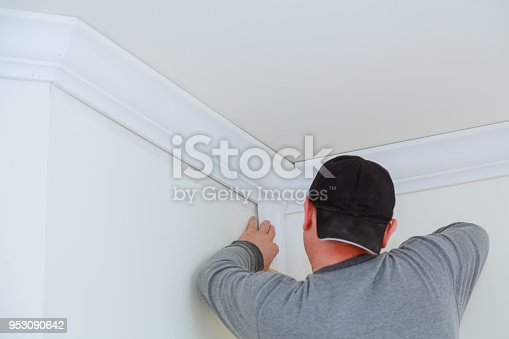 istock Installation of ceiling detail of corner crown molding 953090642