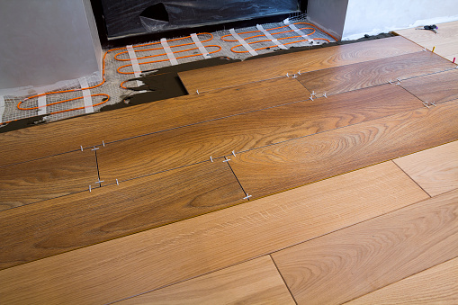 istock Installation of ceramic tiles and heating elements in warm tile floor. Renovation and improvement concept. 958697836
