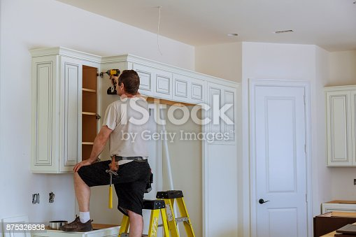 istock Installation of doors on kitchen cabinets 875326938