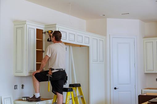 istock Installation of doors on kitchen cabinets 875326938