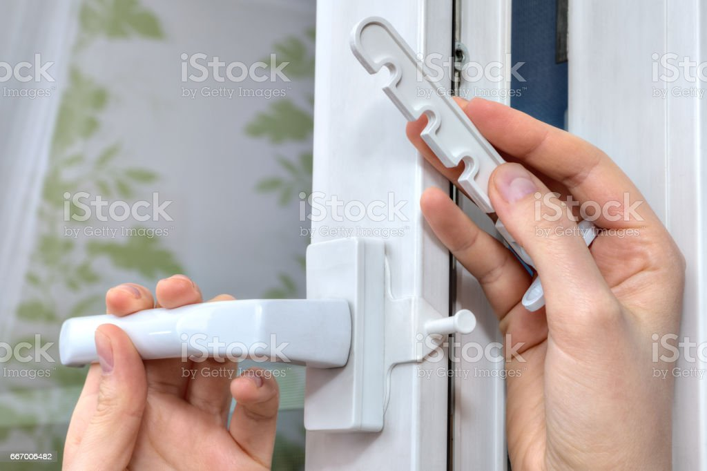 Installation of opening limiter on the pvc window, close-up. stock photo