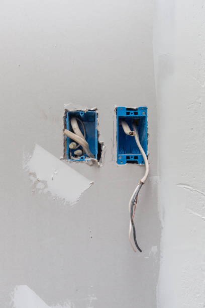 Installation of Outlet and Light Switch - wires exposed. Construction site of new home build. DIY Home improvement, electrical wiring. stock photo