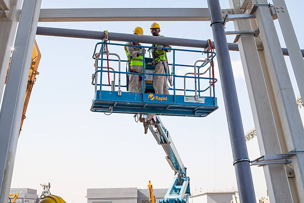 Installation of Pipes using an access platform Al Ain, United Arab Emirates - April 27, 2016 - Two workers installing pipes on an access platform  mobile crane stock pictures, royalty-free photos & images