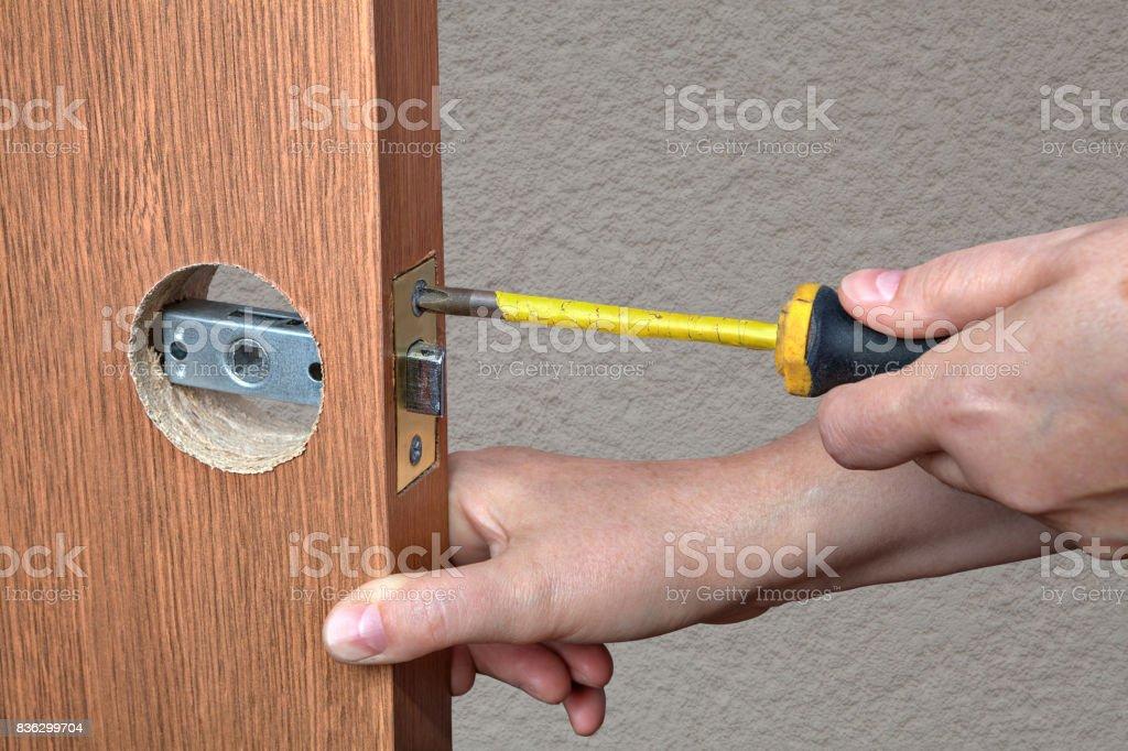 Installation of the door lock, a locksmith hand close-up. stock photo