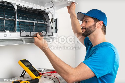 istock Installation service fix  repair maintenance of an air conditioner indoor unit, by cryogenist technican worker checking the air filter in blue shirt baseball cap 1169452224