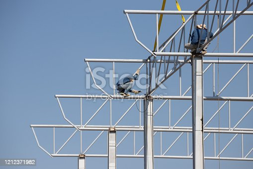 installation steel roof and structure. worker welding the steel truss of roof.
