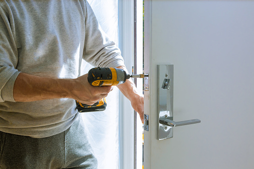 istock Installation with a lock in the door leaf using an drill screwdriver 1185101517