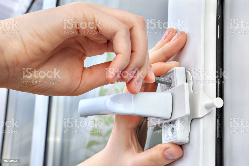 Installer installs  limiter for PVC window, he screwed screw, close-up. stock photo