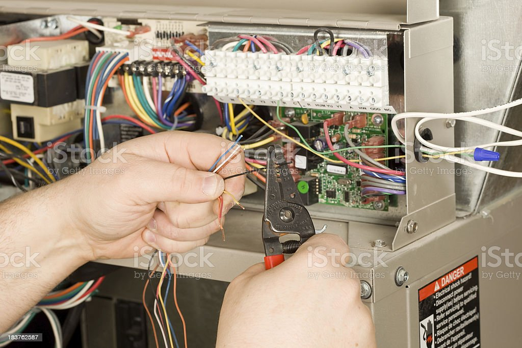 HVAC Installer Strips Small Wires for a new Residential Furnace stock photo