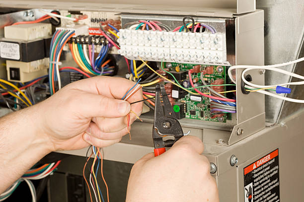 hvac installer strips small wires for a new residential furnace - furnace stock photos and pictures