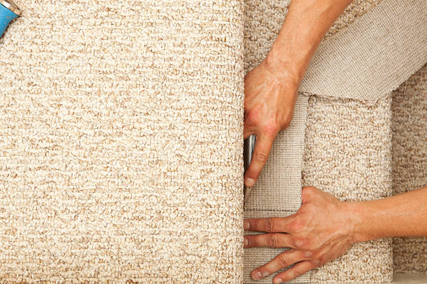 Installer Trimming New Stair Carpet stock photo