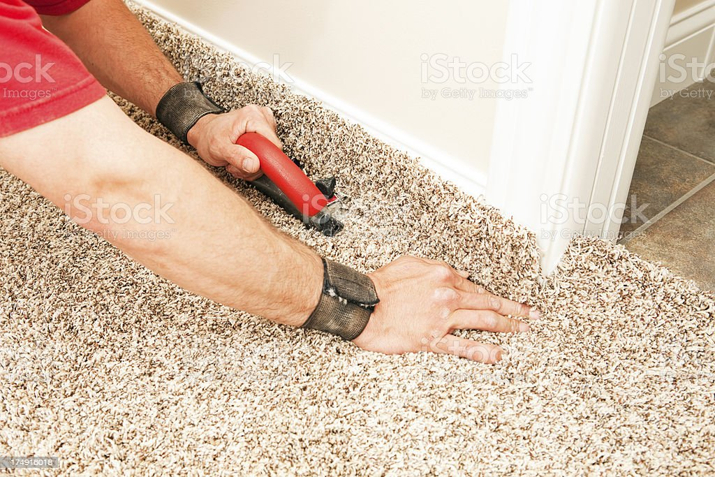 Installer Using Carpet Cutter on New Bedroom Floor royalty-free stock photo
