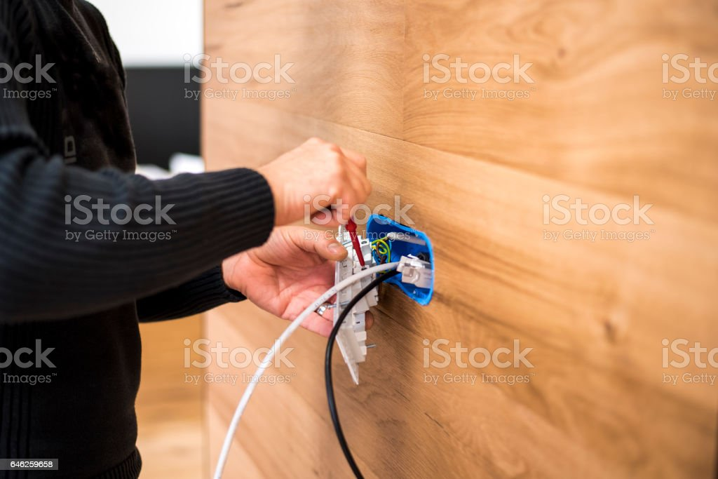 Installing an electrical outlet stock photo