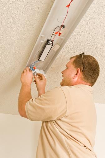 Installing or repairing energy-efficient fluorescent lighting.  Copy space top left.