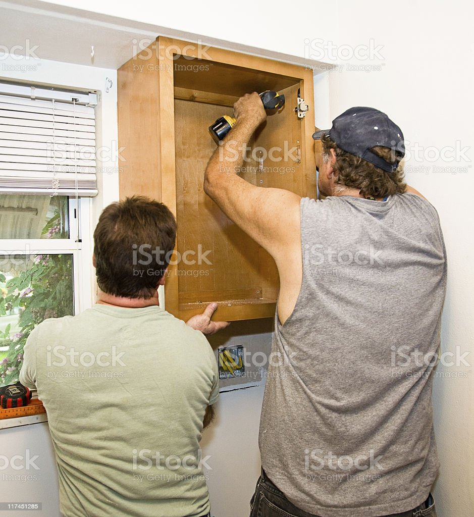 Installing Cabinets - Teamwork royalty-free stock photo