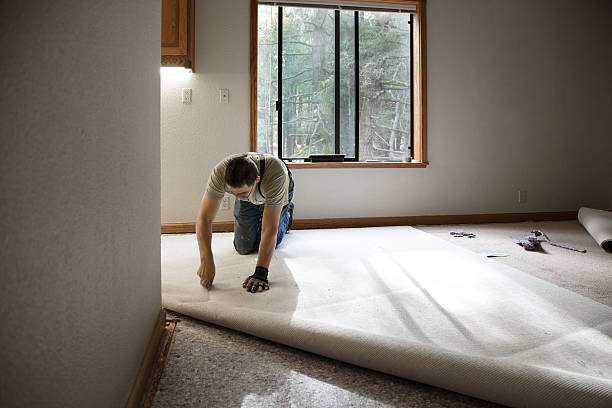 Installing Carpeting Man installing carpeting in home. padding stock pictures, royalty-free photos & images