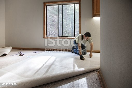 Man installing carpeting in home.