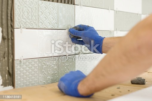 istock Installing ceramic tiles on the wall in kitchen. Placing tile spacers with hands, renovation, repair, construction. 1136413151