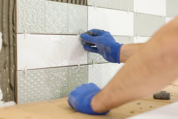 Instalación de azulejos cerámicos en la pared en la cocina. Colocación de espaciadores de azulejos con las manos, renovación, reparación, construcción. - foto de stock