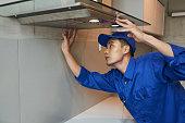 Young Vietnamese technician installing extractor hood